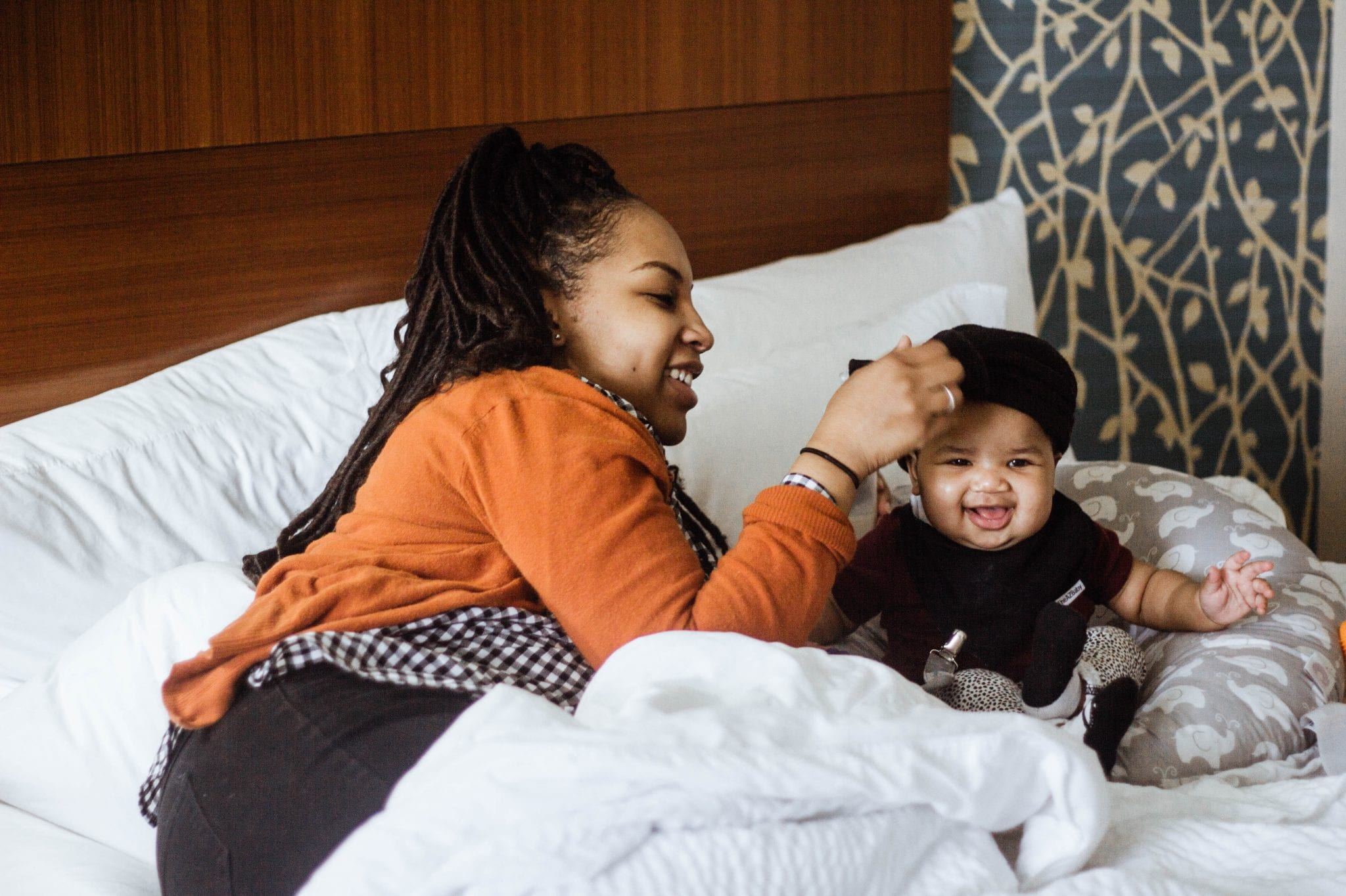 Black Mother and Her Baby Smiling With Mama fixing the baby's hat while sitting in hotel room