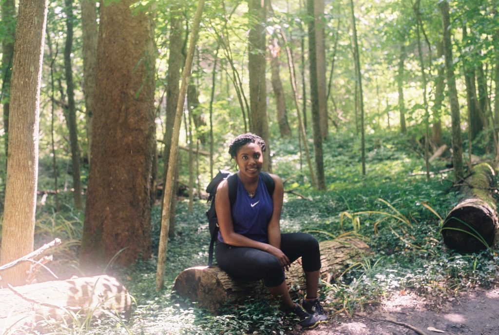 Black woman sitting on log during family hike in Ithaca, NY Portra 400 35mm