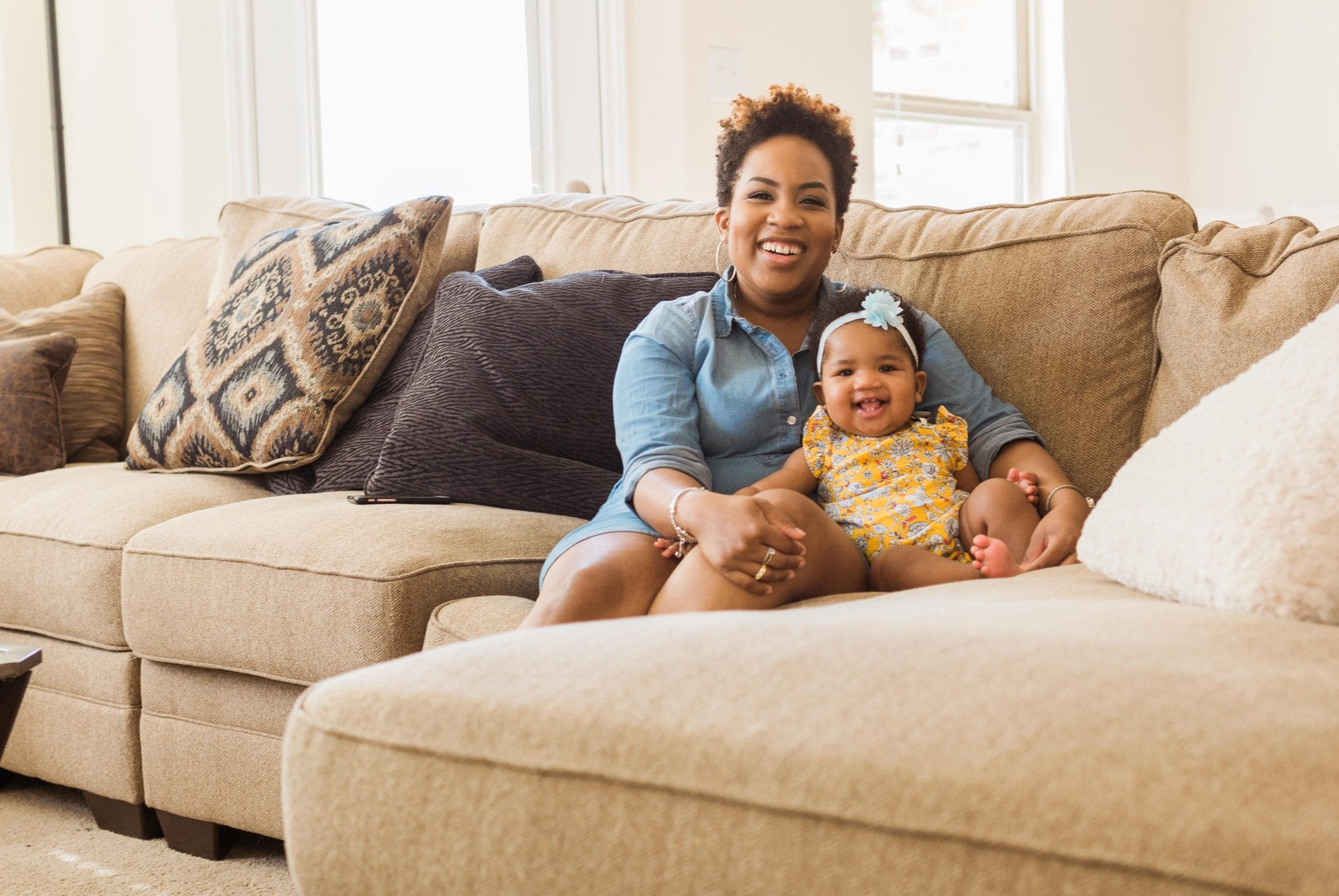 Natural hair Black Mother and infant daughter sitting on couch close to each other for in home session in Houston Texas