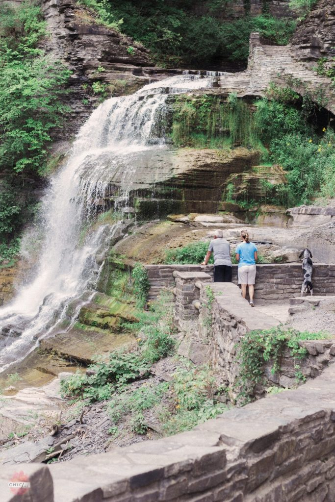Couple standing at top of upstate New York waterfall with their dog during their family hike